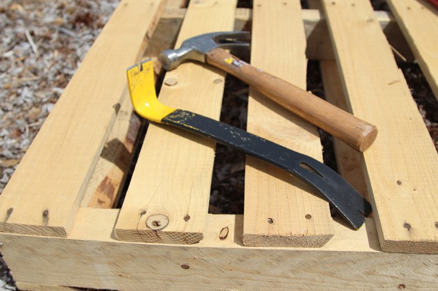 disassemble pallet using hammer and pry bar