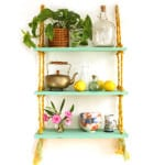 Easy to build and hang, this beautiful gold and turquoise DIY rope shelf is also collapsible. All you need is a drill to build it!