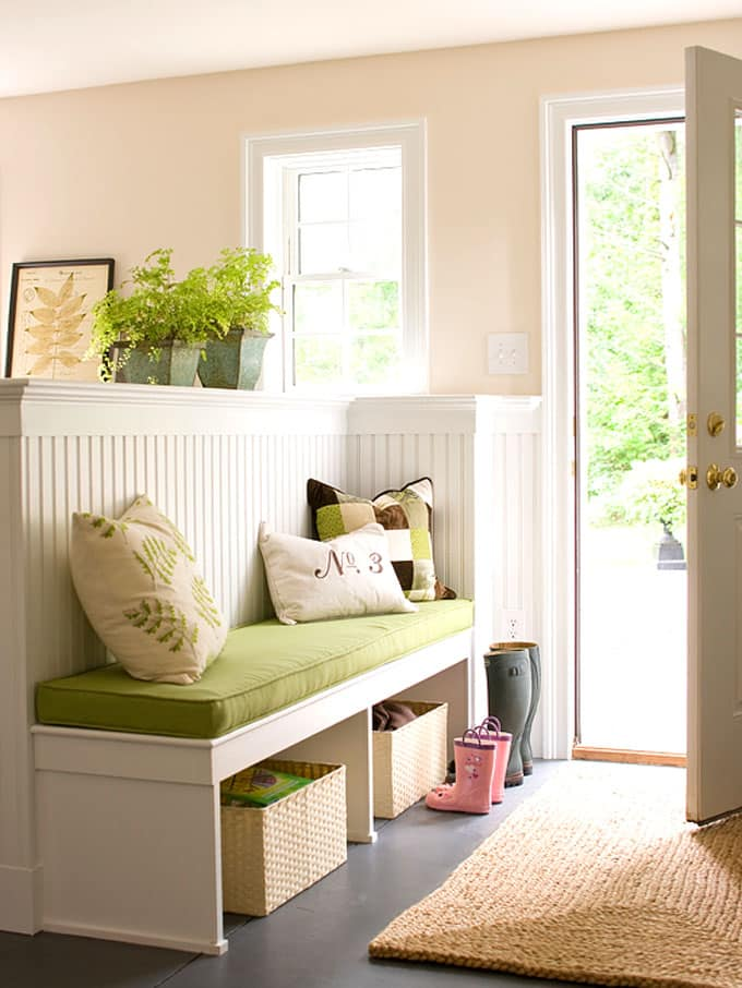 white entryway bench with storage and green cushion