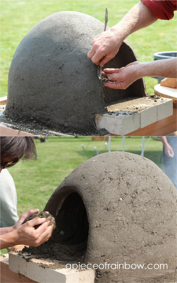 shaping doorway on DIY wood fired outdoor pizza cob / earth oven