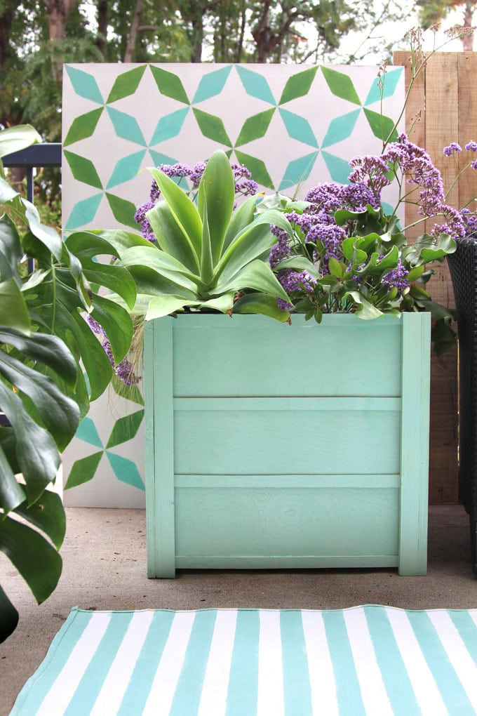 Beautiful DIY planter boxes easily for $10, using simple tools. Lightweight, portable, and long lasting, these large planter pots look amazing on a patio or deck. Free planter box plans included!