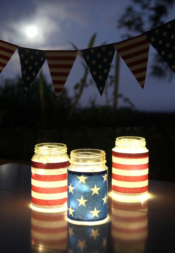 backyard night table with  blue red white stars and stripe american flag inspired july 4th mason jar lights table centerpiece