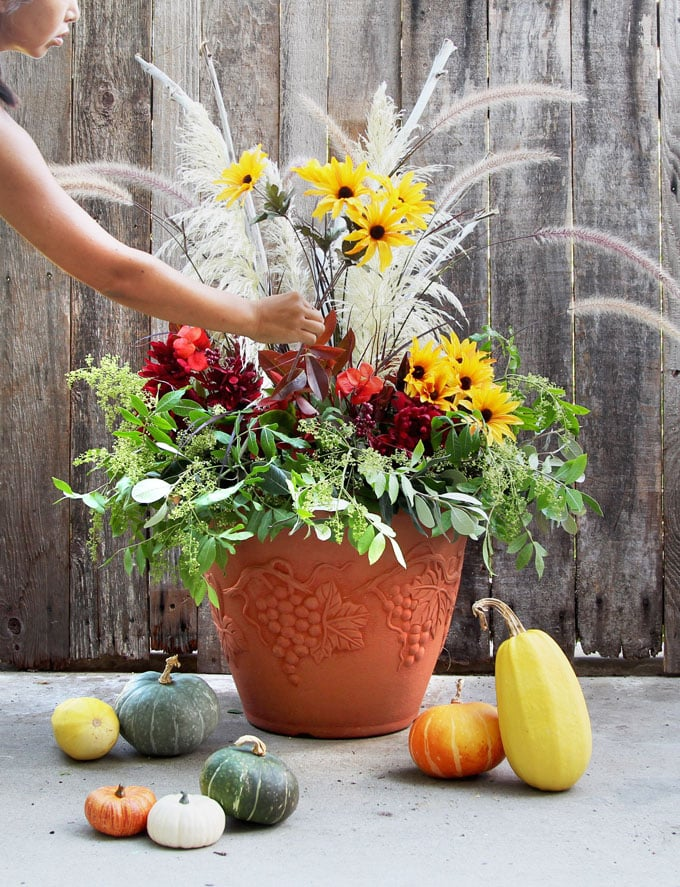 add yellow sunflowers (Dollar store flowers) to colorful outdoor fall & Thanksgiving Decorations planter