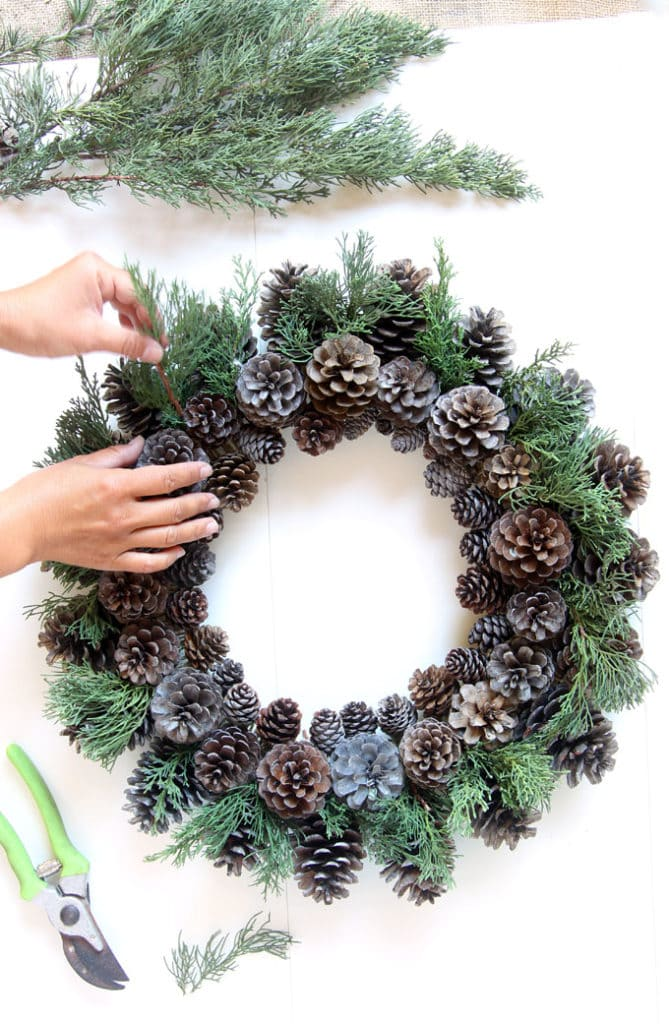 adding conifer greens to DIY pinecone wreath