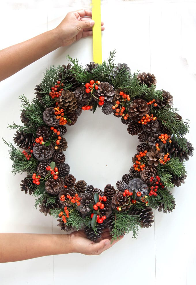 To make a Christmas pine cone wreath, tuck in some sprigs of real or artificial red berries among the pine cones and evergreen foliage.