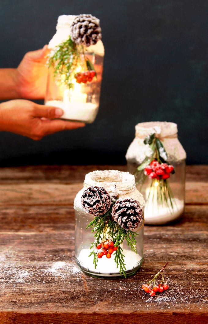 snow covered Christmas DIY mason jar centerpieces with candles, pine cones, red berries