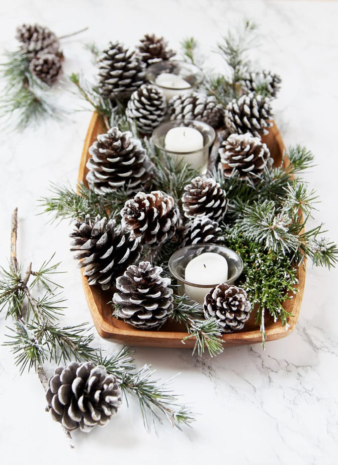 farmhouse table decorations with candles and DIY snow covered pine cones & branches in wood tray