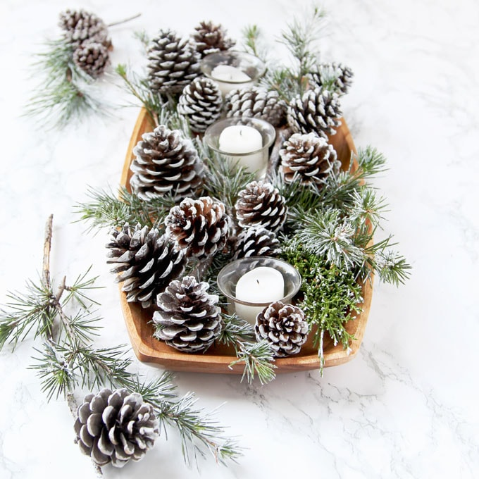 white table decorations with candles and DIY snow covered pine cones & branches in wood tray