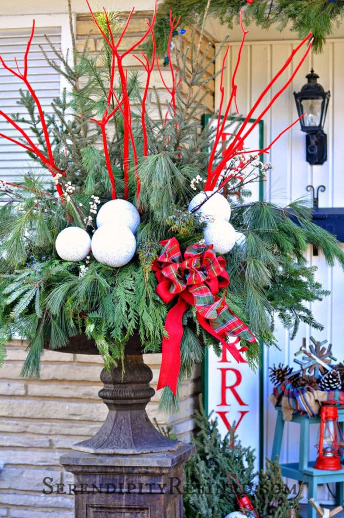 painted red branches in a Christmas planter urn
