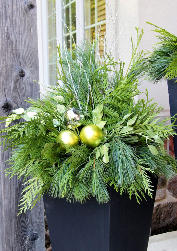 Chartreuse green ornaments in winter planter