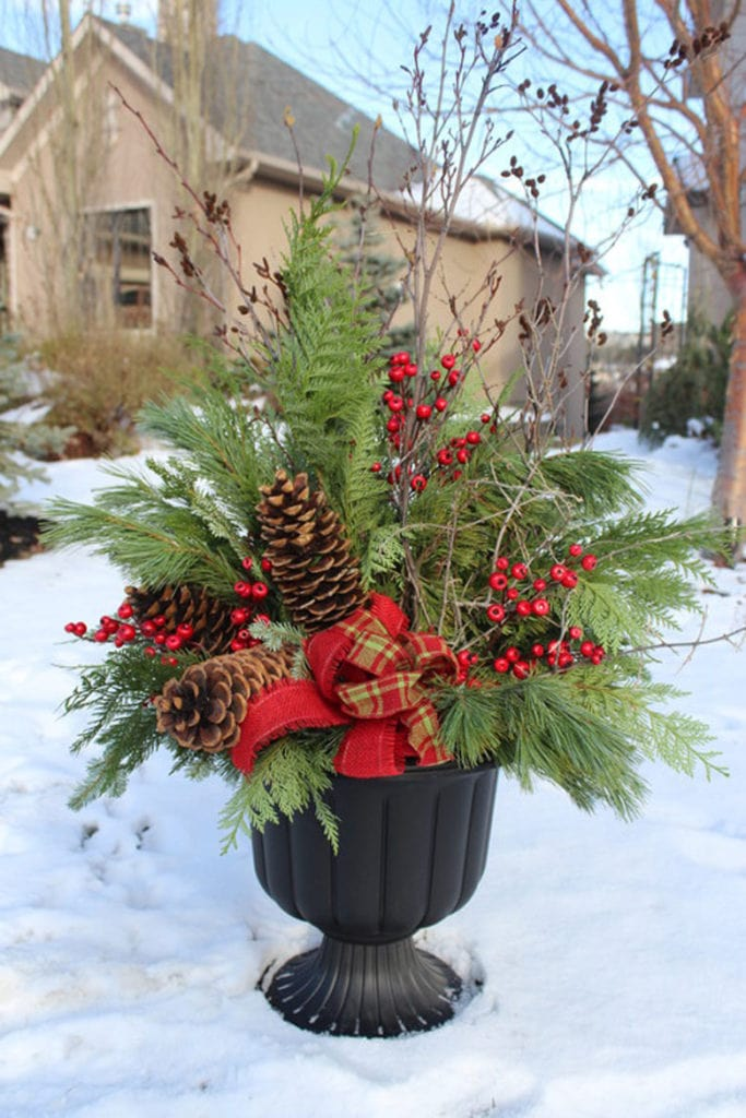 classic urn planter with evergreens and berries for Christmas outdoor decorations
