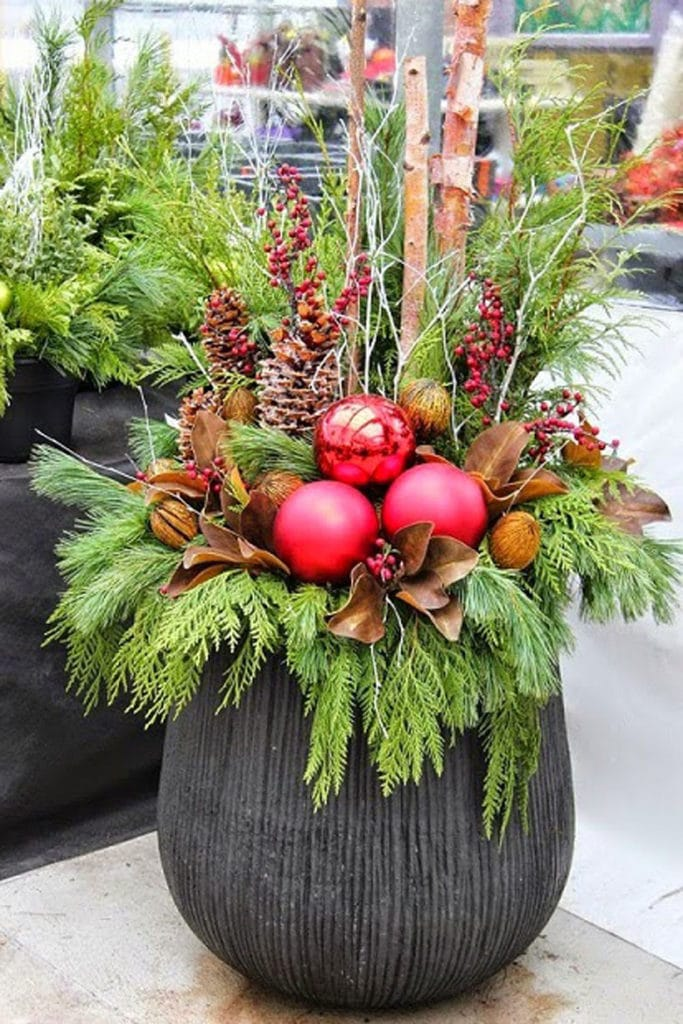 colorful Christmas ornaments in outdoor winter planter