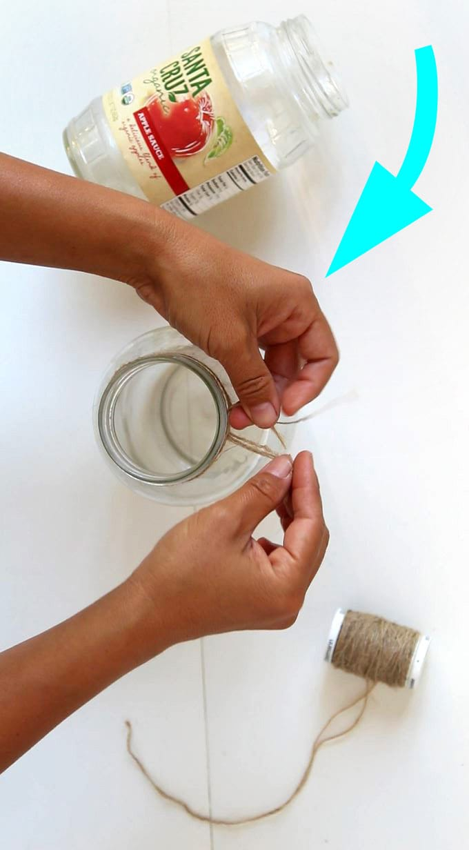 She wraps twine on the rim of a mason jar. What happens next is STUNNING! Such an incredibly easy and beautiful 5-minute mason jar DIY! #masonjars #masonjarcrafts #recycle #diy #homedecor #homedecorideas #vintage #vintagewedding #weddingdecor #weddingdecorations #craft #crafts #crafting #farmhouse #farmhousedecor #holiday #christmas #christmasdecor #christmasideas #upcycle