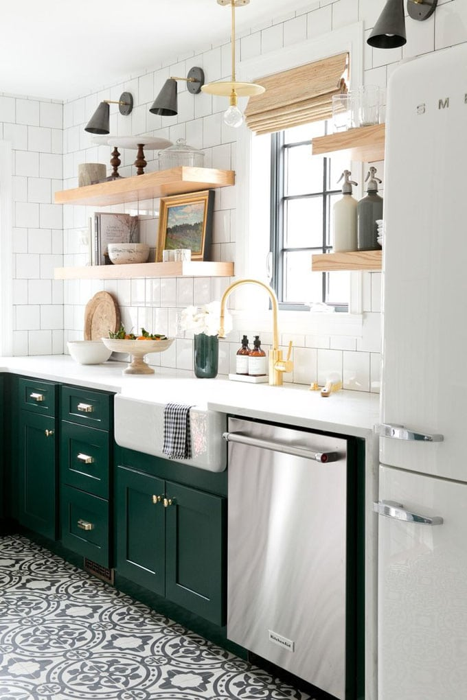 small beautiful kitchen with cement tile floor, white square subway tile backsplash, forest green cabinets, farmhouse loght fixtures, brass faucet, wood open shelves