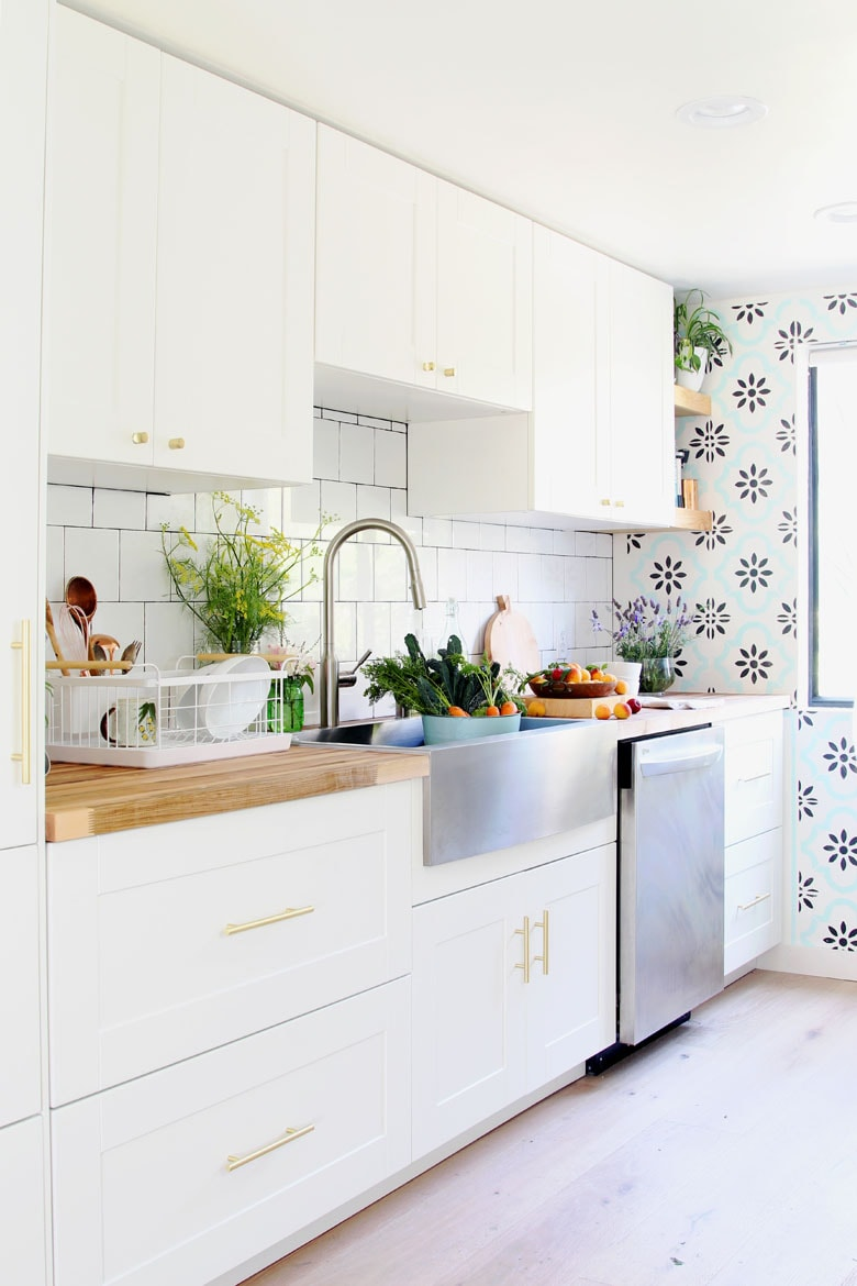 boho kitchen decor , stainless farmhouse sink and butcherblock countertop in white ikea kitchen remodel