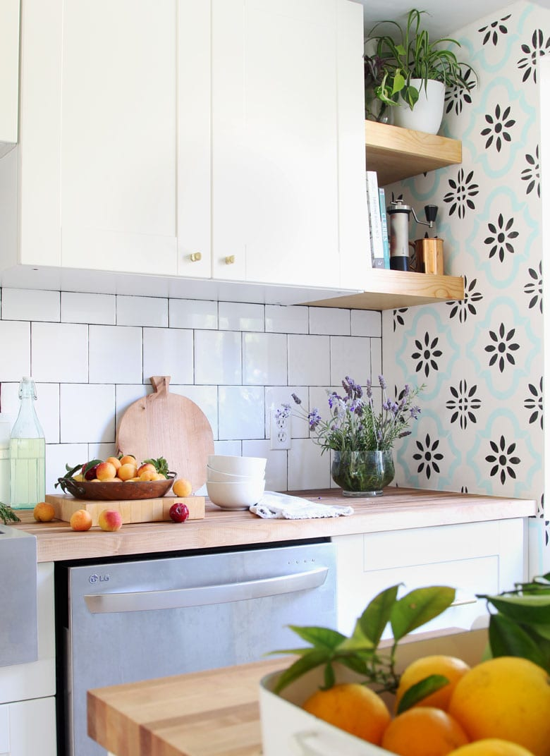 farmhouse ikea kitchen with boho anthropologie style kitchen decor, open shelving, and butcherblock countertop