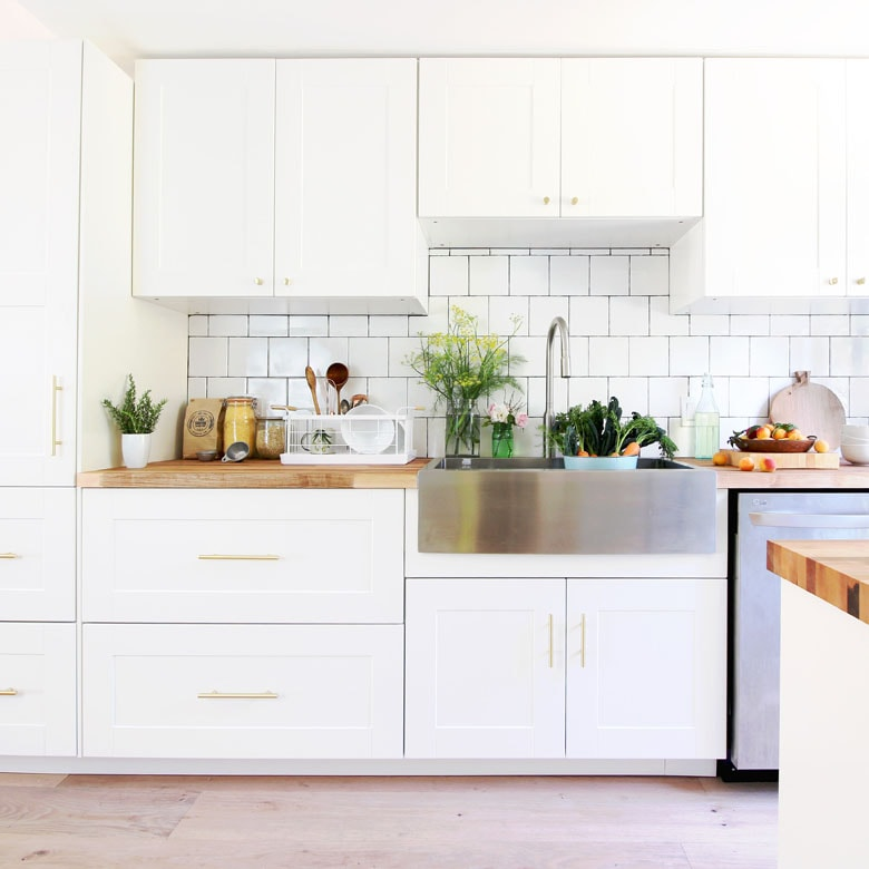 white ikea kitchen with farmhouse sink and butcherblock countertop