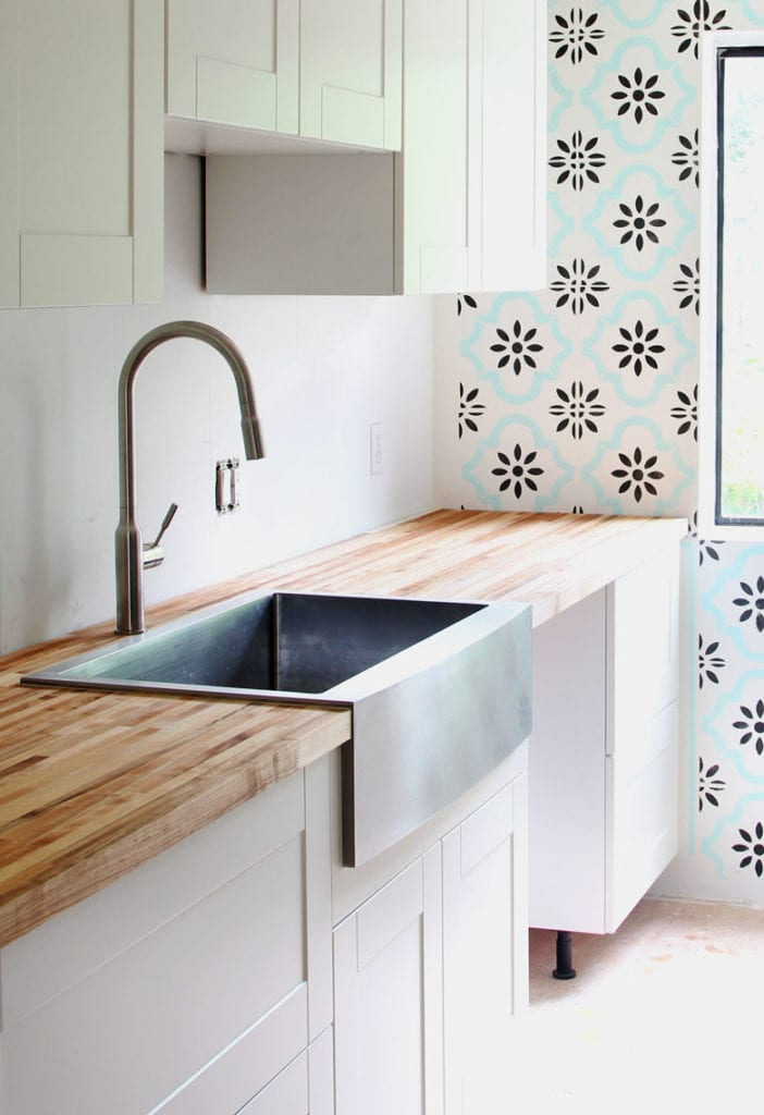 large stainless steel farmhouse sink and butcher block counter in ikea kitchen