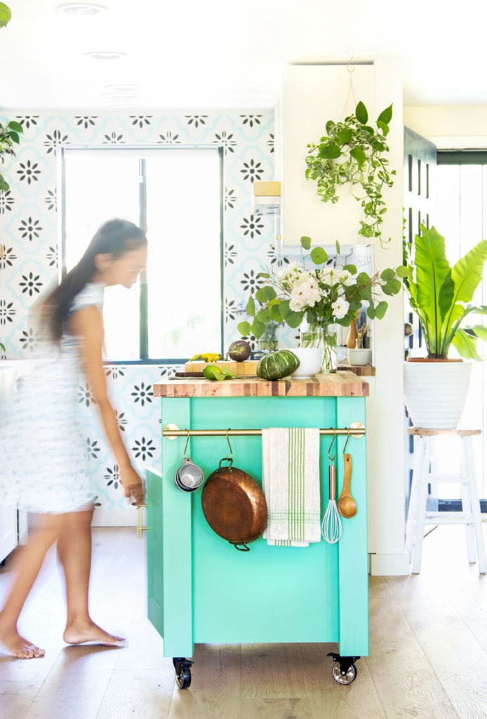 bright and airy farmhouse kitchen with green kitchen island cart on wheels, and towel bar