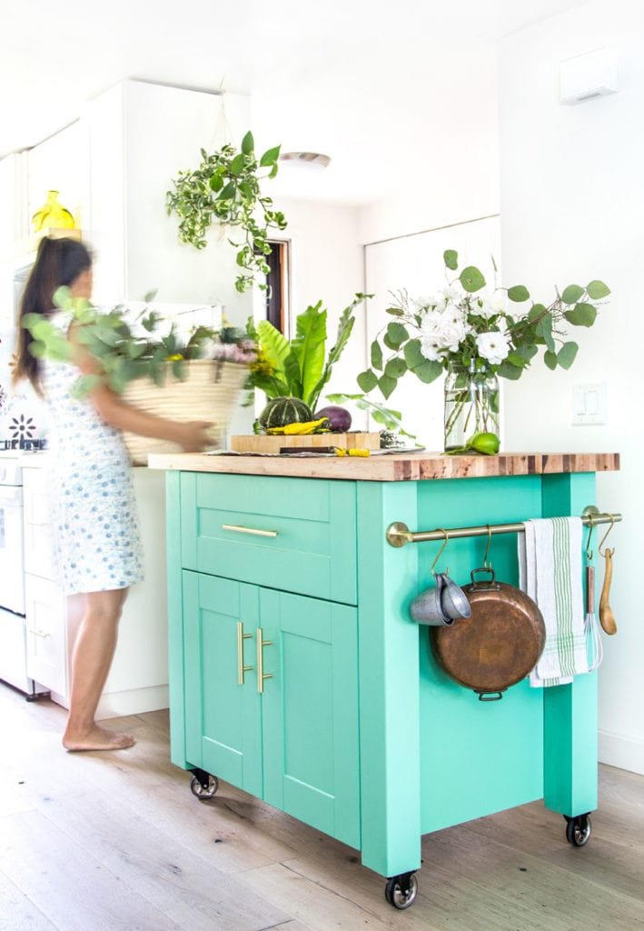 beautiful modern farmhouse kitchen with bohemian style colorful kitchen island, portable kitchen cart on wheels with hanging rail