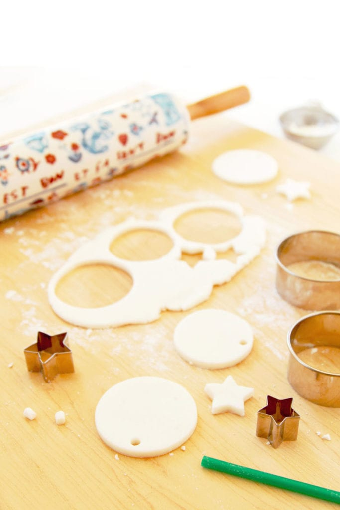 rolling and cutting baking soda clay and cornstarch clay to make Christmas ornaments