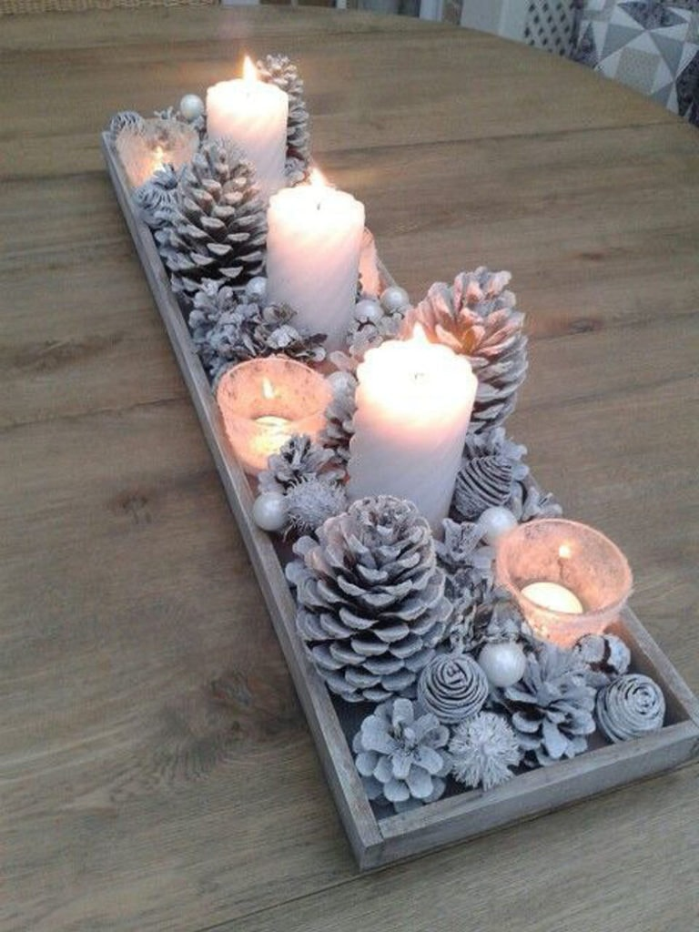 Snowy Christmas table centerpiece ideas with white pine cones in wood tray