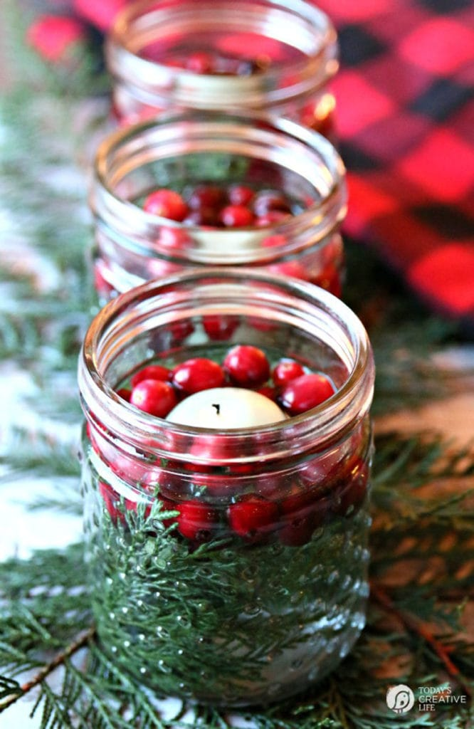 a floating tea candle in a jar filled with cranberries, conifers, and water. This would make a great Thanksgiving centerpiece