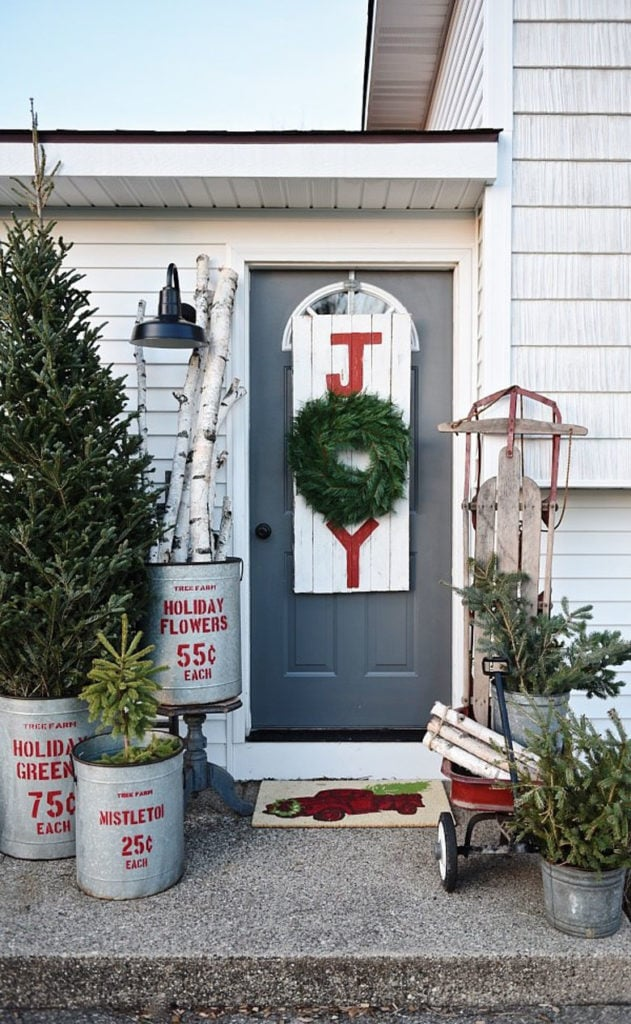 Vintage style galvanized tin buckets with conifer branches and pine cones as  farmhouse Christmas outdoor decorations