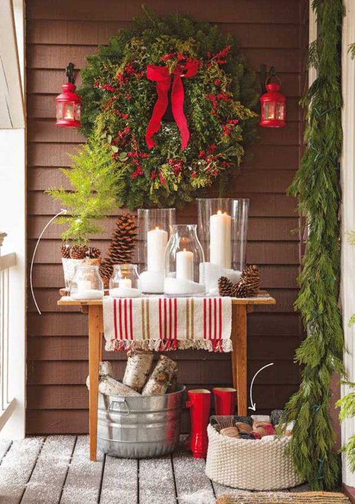 Use a table to display Christmas candles and pine cones on the front porch