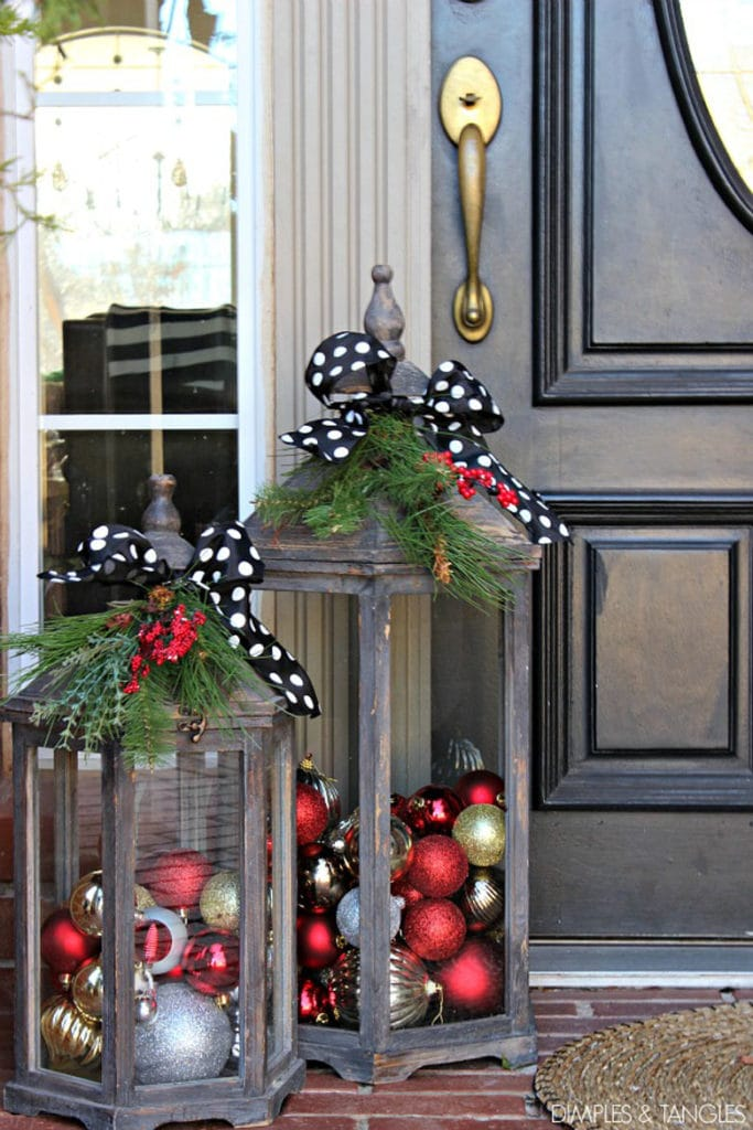 Wood lanterns filled with Christmas ornaments make beautiful decorations for the front porch
