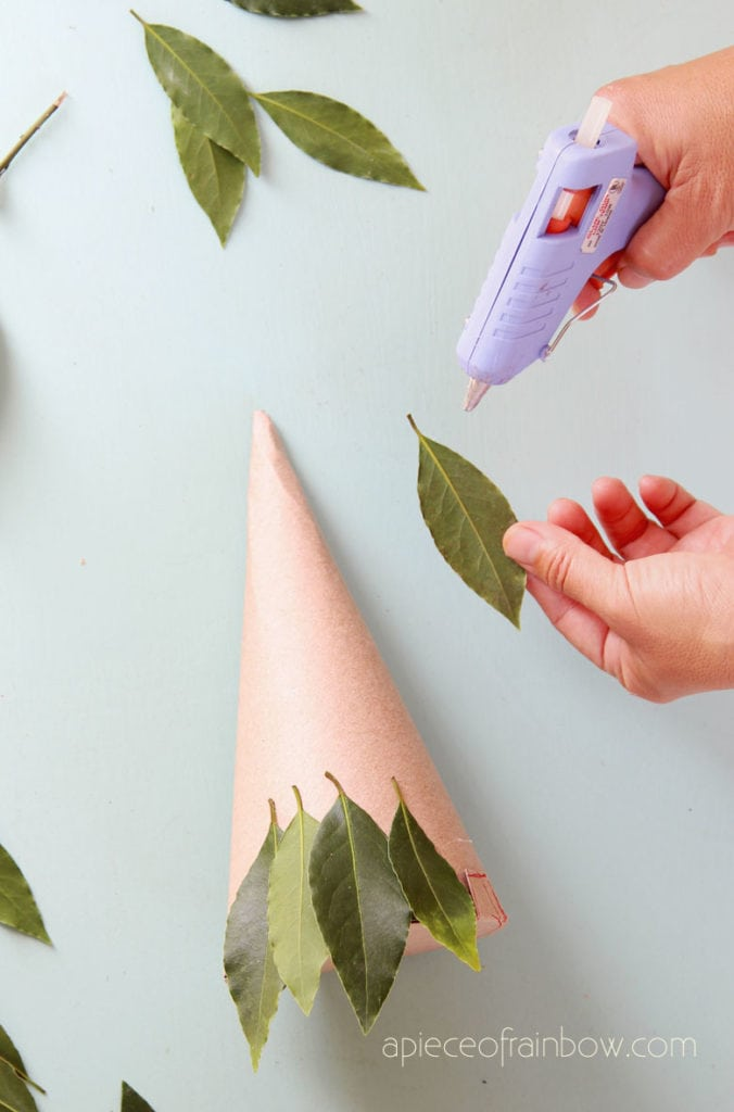 glue leaves to cardboard cone to make Christmas tree craft