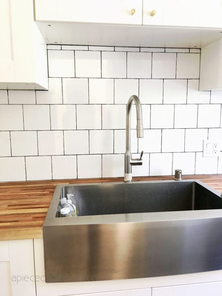 modern farmhouse IKEA kitchen with white cabinets, farmhouse sink, modern subway tile, butcher block countertop,