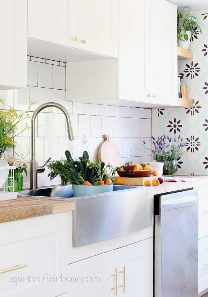 bohemian farmhouse white DIY IKEA kitchen remodel with floating shelves , farmhouse sink, and square subway tile backsplash