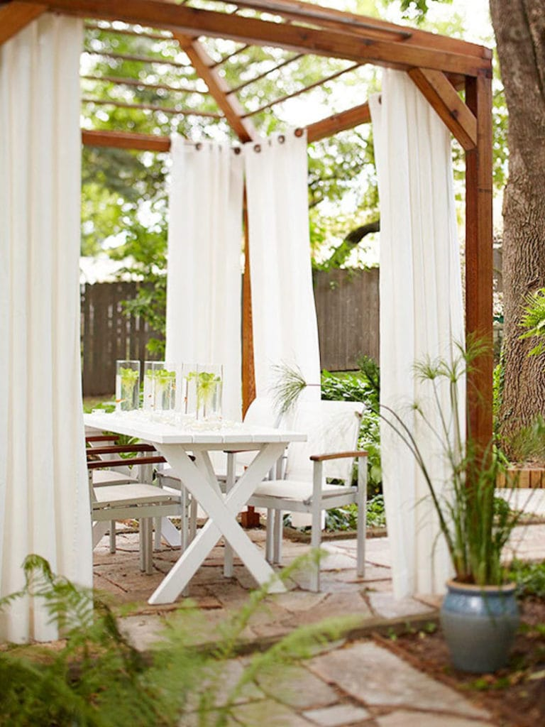 white fabric curtains on outdoor wood pergola