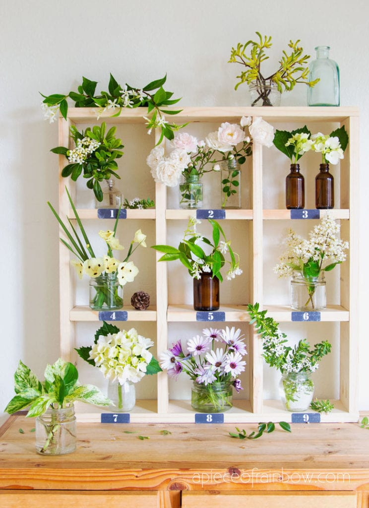 bohemian decorations with vintage bottles and flowers on farmhouse cubby wall shelf