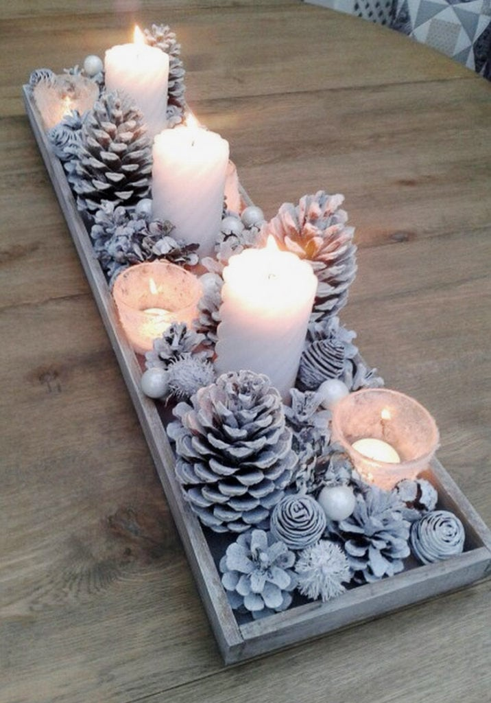 a tray of white snowy pine cones with candles as table decorations