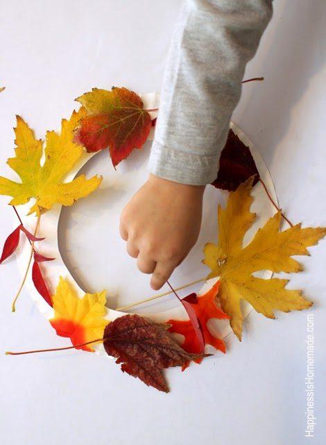pegar hojas en un plato de papel cortado para hacer una corona de otoño