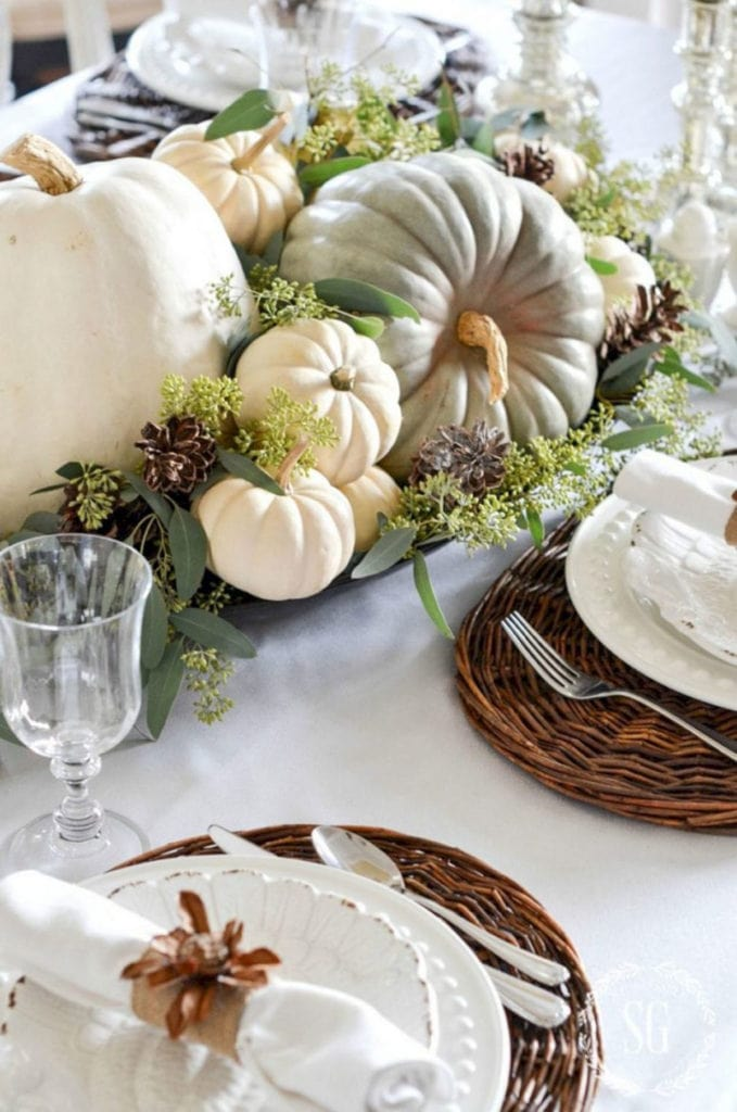 table settings with green, blue and white pumpkins, olive & eucalyptus branches, gold autumn berries, pine cones.