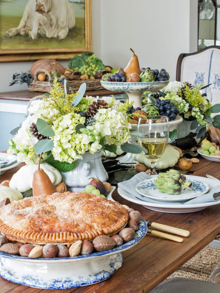 Autumn harvest Thanksgiving table decorations with apples, pears, figs, grapes, nuts, vegetables like artichokes, squash, mixed with flowers!