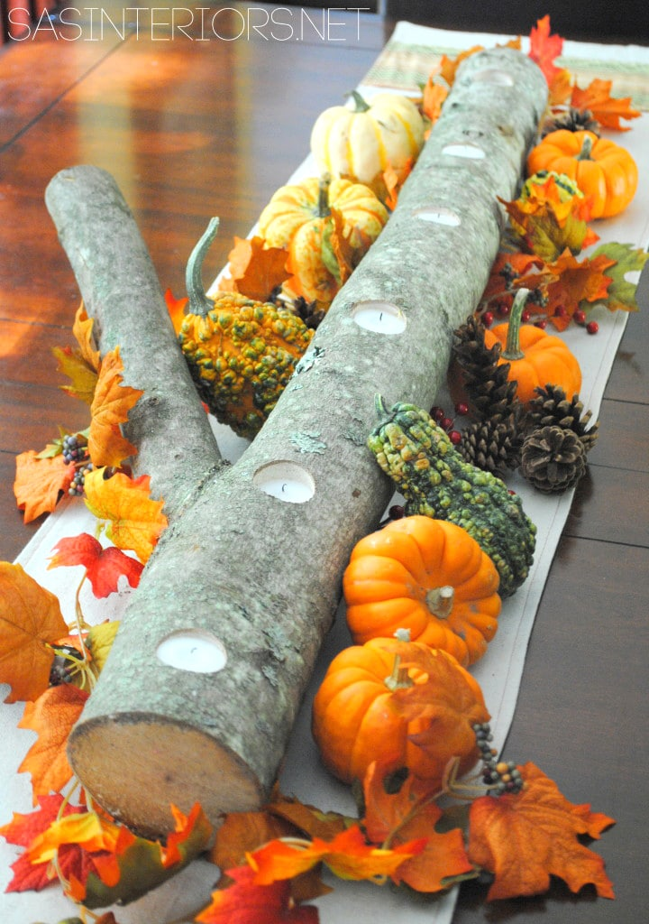 unique DIY log candle holder with fall leaves, mini pumpkins and gourds on Thanksgiving table