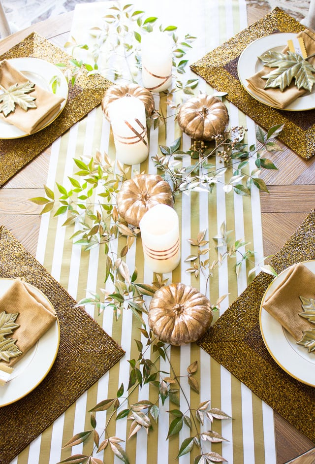 round table decorated for Thanksgiving with Metallic stripe runner, gold glitter placemats , gold pumpkins, candles and linens