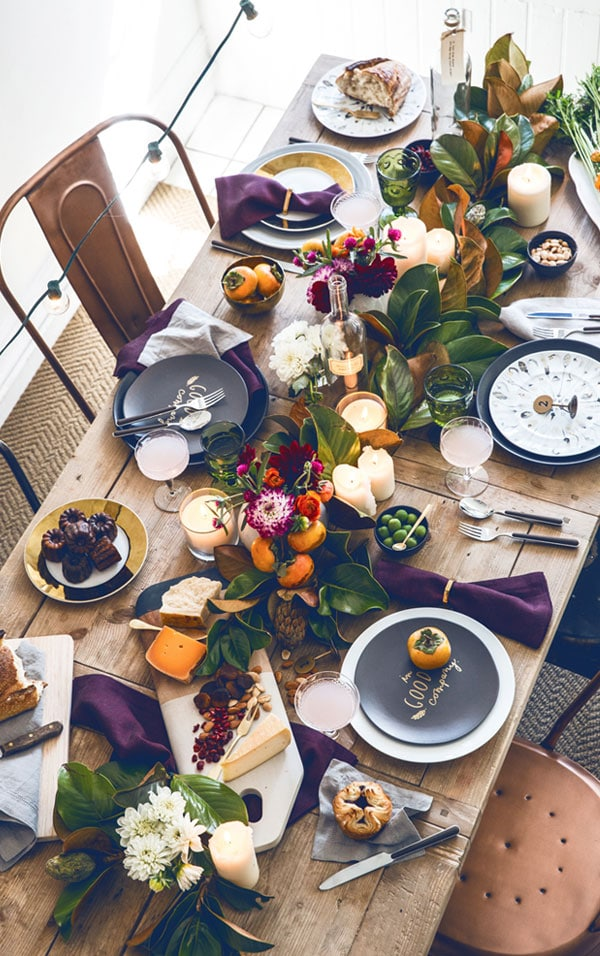 Thanksgiving table with purple napkins and magnolia centerpiece
