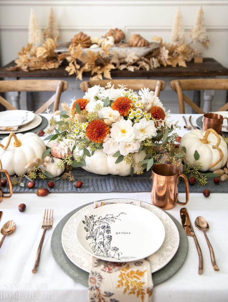 Modern farmhouse white pumpkin vase centerpiece, made with mostly white and a few deep rust orange flowers, and silver green Eucalyptus